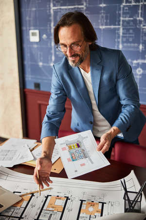 Joyous man sorting out paperwork at his office