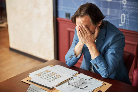 Busy office worker suffering from burnout while doing his job