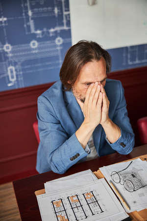Distressed man experiencing fatigue and anxiety at work