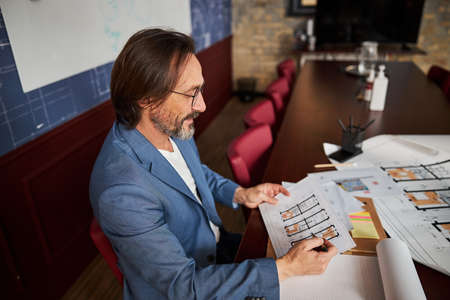 Smart gentleman looking at whiteprints of appartments