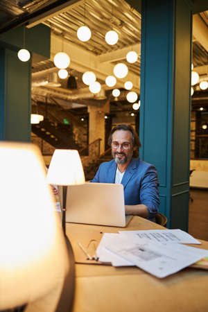 Mirthful gentleman using laptop for doing remote work