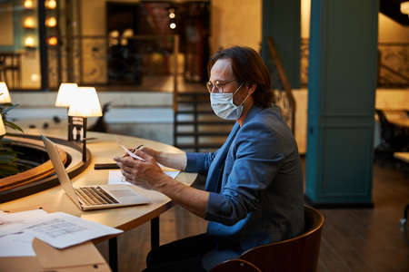 Mindful worker using protective mask while working in public area