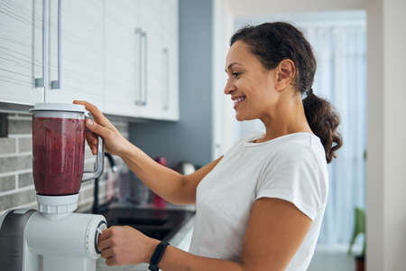 Cheerful woman making a healthy fruit drink