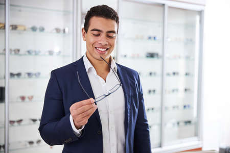 High-spirited customer looking at new glasses in his hands