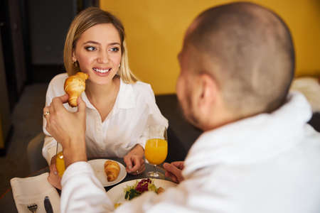 Caring husband sharing his crescent-shaped roll with his wife