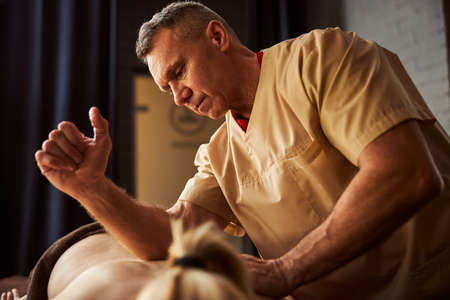 Skilled spa therapist massaging back of woman with his elbow