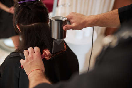 Stylist with hairdressing tools working on a female hairstyle