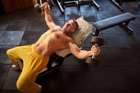 Optimistic sportsman looking energised during dumbbells workout
