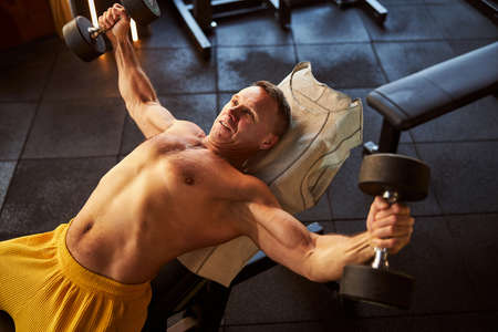 Joyous gentleman using dumbbells for his gym routine