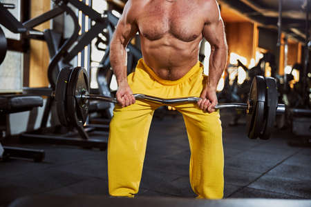 Strong muscled man working out with barbell at gymnasium