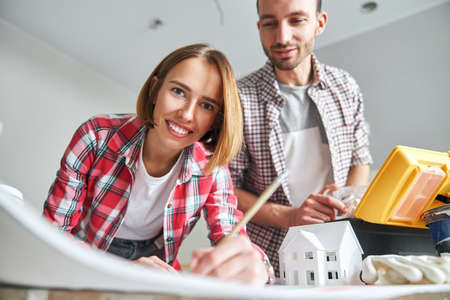 Cheerful attractive draftswoman drawing a house plan