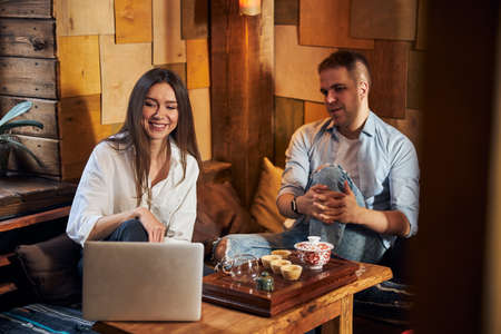 Beautiful young couple using laptop in cozy cafe Imagens