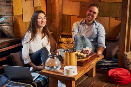 Cheerful young couple spending time together in tea house Imagens