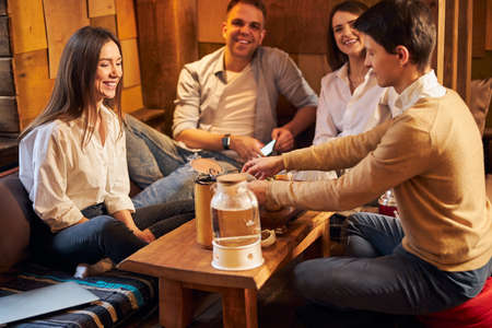Group of friends drinking tea and smiling in cafe Imagens