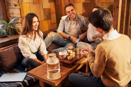 Group of friends chatting and laughing in tea house