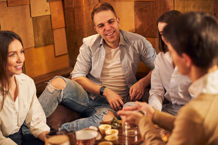 Cheerful young people spending time in tea house Imagens