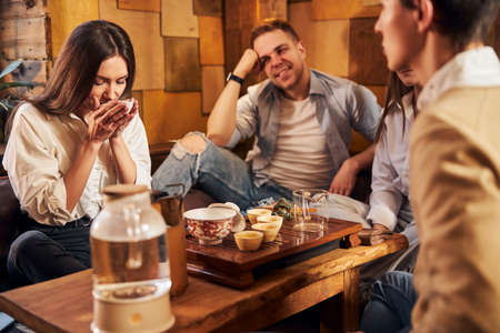 Charming young woman enjoying tea with friends in cafe Stock Photo