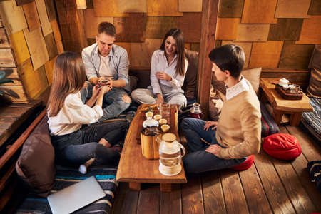 Group of friends enjoying delicious tea in cozy cafe