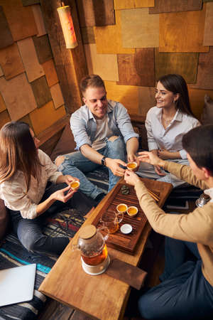 Cheerful young people enjoying tea ceremony in cozy cafe
