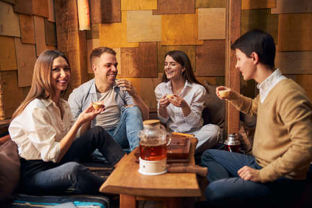 Joyful friends spending time together in tea house
