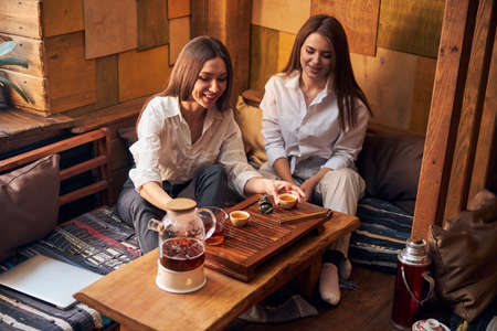 Cheerful young women enjoying tea ceremony in cafe