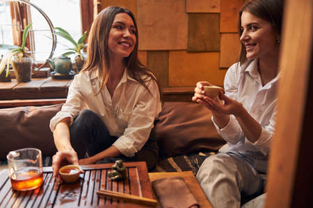Charming young women enjoying tea ceremony in cafe Imagens