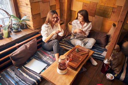 Cheerful young women drinking tea in cozy cafe