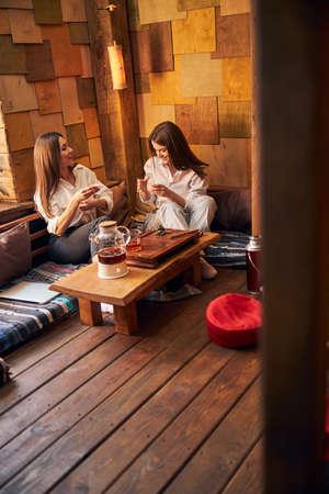 Beautiful young women drinking tea in cozy cafe