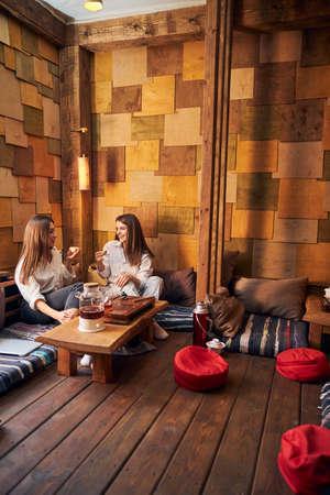 Beautiful young women enjoying tea ceremony in cafe