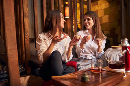 Cheerful female friends drinking tea and chatting in cafe