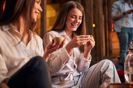 Cheerful young women drinking tea in cafe