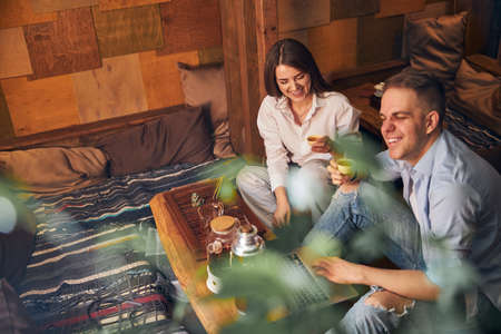 Cheerful man and woman drinking tea and using laptop in cafe Imagens