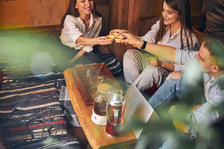 Cheerful friends toasting with tea cups in cafe Imagens