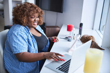Contented Afro-American woman using her laptop at home