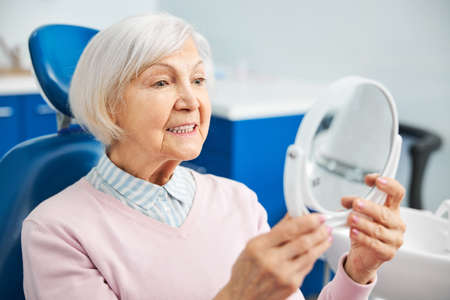 Focused aging female raising table mirror to see teeth