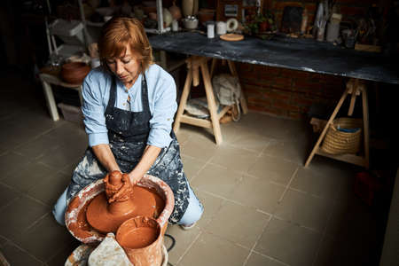 Charming female potter working in pottery workshop Banque d'images