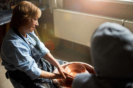 Senior woman making pottery with friend in workshop