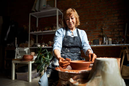 Nice senior woman making clay pot in pottery workshop Banque d'images