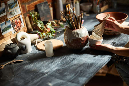 Ceramic artist hands painting pottery in workshop