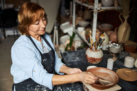 Charming old woman ceramist painting clay bowl in workshop