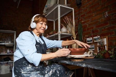 Female potter in headphones working in art pottery studio