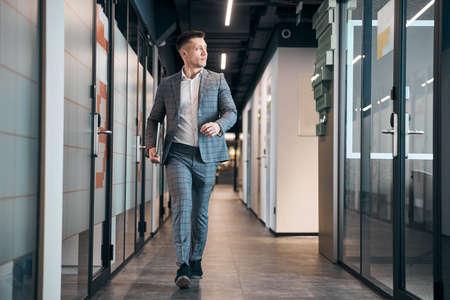 Stylish young man walking down the hallway