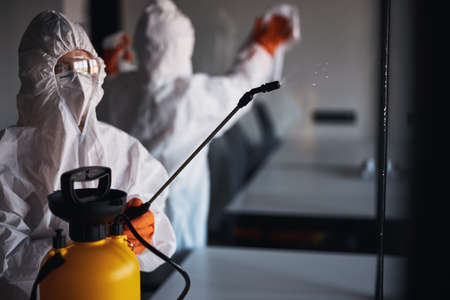 Two people in protective gear cleaning the glass walls