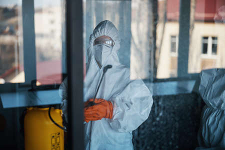 Janitor in protective gear standing before the office glass wall Standard-Bild