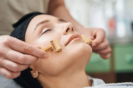 Cosmetician massaging the client face with acupressure metal roller massagers