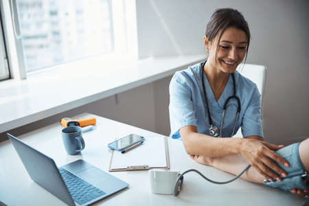 Cheerful female doctor checking patient blood pressure in clinic