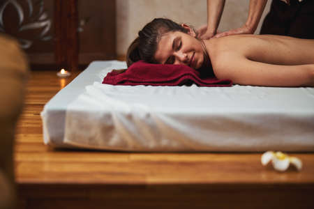 Female lying with face on red towel during massage