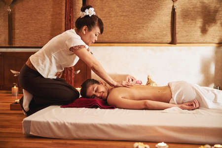 Skilled massage expert stroking woman back with hands Stock Photo