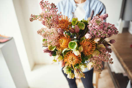 Floral designer holding a bunch of showy spring flowers Imagens