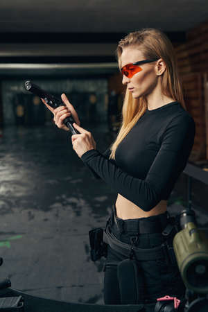 Focused young female shooter concentrated on loading the gun